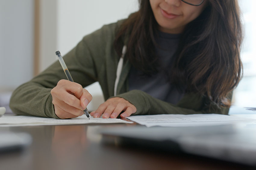 woman-write-on-the-report-study-for-the-exam-at-ho-ZKRG588